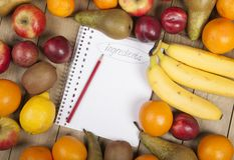 Bleistift auf Buch admist Früchten Stockbilder