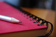 Bleistift auf rotem Notizbuch Stockfotografie