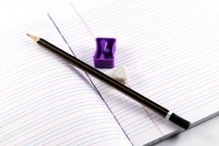 Bleistift, Bleistiftspitzer, Radiergummi, Buch Stockbild