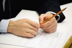 Bleistift in der Hand und Notizbuch Lizenzfreies Stockfoto