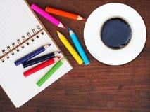 Bleistift des offenen Buches und der Farbe und ein Tasse Kaffee auf hölzernem backgro Stockfotos