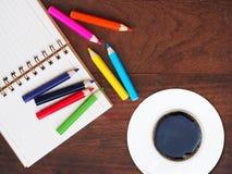 Bleistift des offenen Buches und der Farbe und ein Tasse Kaffee auf hölzernem backgro Lizenzfreie Stockbilder