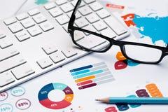 Bleistift, Gläser und Tastatur auf Diagramm berichten über Hintergrund Stockfotos