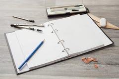 Bleistift, Kompass, Radiergummi, Bleistiftspitzer, ein Zeichnungsbuch mit einem Bleistift Lizenzfreie Stockfotografie