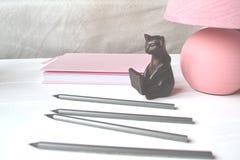 Bleistift, Lampe, Notizbuch und Elemente des Dekors auf dem Tisch Schöner Arbeitsplatz Stockbilder