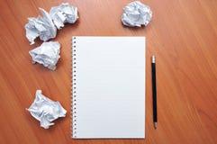 Bleistift liegt auf der Notizbuchseite um das zerknitterte Papier stockfotos