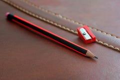 Bleistift mit dem Bleistiftspitzer lokalisiert auf ledernem Hintergrund Lizenzfreies Stockbild
