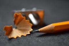 Bleistift mit Schnitzeln und des Bleistiftspitzers Abschluss oben stockfotografie