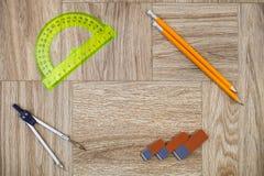 Bleistift-, Radiergummi-, circinus- und Winkelmessermachthaber auf einer hölzernen Beschaffenheit Lizenzfreies Stockbild