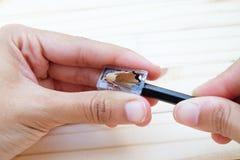 Bleistift rasiert durch Bleistiftspitzer und beide Hände Stockfotos