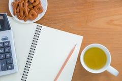 Bleistift, Taschenrechner, Notizbuch, Snack und Getränk stockfotografie
