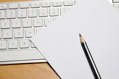 Bleistift, Tastatur und Papier auf Tabelle Lizenzfreies Stockbild
