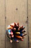Bleistift-Topf vieler Farben von oben genanntem auf hölzerner Planken-Tabelle Lizenzfreies Stockfoto