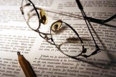 Bleistift u. Gläser über geöffnetem Buch Stockfotografie