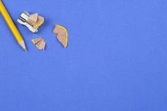 Bleistift und Bleistiftspitzer auf einem blauen Hintergrund Lizenzfreie Stockfotos