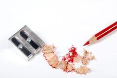 Bleistift und Bleistiftspitzer mit dem Bleistiftrasieren lokalisiert auf weißem Hintergrund Lizenzfreie Stockfotografie