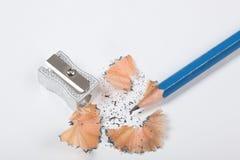 Bleistift und Bleistiftspitzer mit dem Bleistiftrasieren lokalisiert auf weißem Hintergrund Stockfotografie