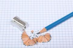 Bleistift und Bleistiftspitzer mit dem Bleistift, der Rest auf Quadrate rasiert, bedecken Stockbilder
