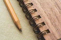 Bleistift und gewundenes Notizbuch auf dem Segeltuchhintergrund Stockbild