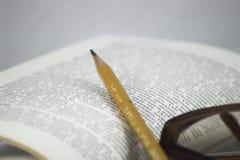 Bleistift und Gläser auf einem Buch Stockfoto
