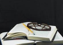 Bleistift und Gläser auf einem Buch Stockbild