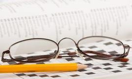 Bleistift und Gläser auf einem Kreuzworträtsel Lizenzfreie Stockfotografie