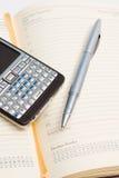 Bleistift und intelligentes Telefon auf Terminkalender Stockfotos