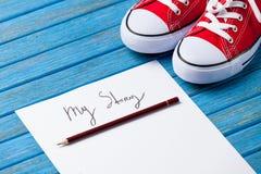 Bleistift und Papier mit meiner Geschichte fasst nahe Gummiüberschuhen ab Lizenzfreie Stockfotos