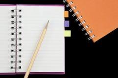 Bleistift und Post-It gesetzt auf Mininotizbuch Lizenzfreies Stockfoto