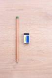 Bleistift und Radiergummi auf hölzernem Hintergrund Stockbilder
