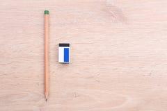 Bleistift und Radiergummi auf hölzernem Hintergrund Lizenzfreies Stockbild