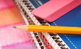 Bleistift und Radiergummi, die auf Notizbüchern stillstehen Stockbild