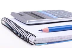 Bleistift und Rechner auf Papiernotizbuch Lizenzfreies Stockfoto