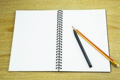 Bleistift und Stift auf dem Notizbuch Stockfoto