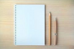 Bleistift und Stift mit Notizblock Stockbild