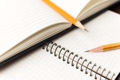 Bleistifte auf den Seiten eines offenen Notizbuches für Aufzeichnungen stockfotos