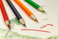 Bleistifte auf einem Hintergrund von Kind-` s Zeichnungen mit der Lehrer ` s Einschätzung Stockfotografie