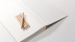Bleistifte auf einem leeren Anmerkungsbuch Lizenzfreie Stockfotos