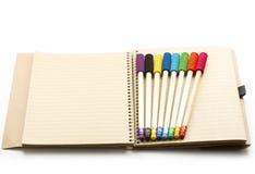 Bleistifte auf Notizbuch Stockfotografie