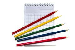 Bleistifte auf Schreibenbuch auf Weiß Stockfoto