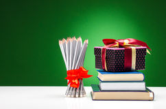 Bleistifte, Bücher und ein Geschenk Lizenzfreie Stockfotos