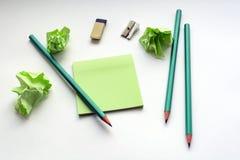 Bleistifte, Bleistiftspitzer, Radiergummi, Aufkleber, auf einer weißen Tabelle mit zerknitterten klebrigen Anmerkungen, kreative  Lizenzfreies Stockfoto