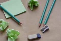 Bleistifte, Bleistiftspitzer, Radiergummi, Aufkleber, braunes Papier mit zerknitterten klebrigen Anmerkungen, kreative Krise, Ver Stockfoto