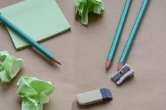 Bleistifte, Bleistiftspitzer, Radiergummi, Aufkleber, braunes Papier mit zerknitterten klebrigen Anmerkungen, kreative Krise, Ver Lizenzfreie Stockfotos
