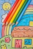 Bleistifte der Regenbogenfarben auf Zeichnung des Kindes Lizenzfreies Stockfoto