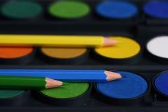 Bleistifte des blauen Grüns und des Gelbs liegen auf bunten Farben für das Zeichnen Stockfotos