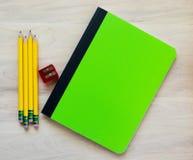 4 Bleistifte, ein Bleistiftspitzer und ein Notizbuch mit Blinddeckel für kundengebundene Mitteilung Lizenzfreie Stockfotografie