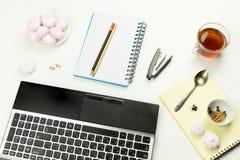 Bleistifte, ein Hefter, Knöpfe, ein Notizblock, Laptop, Eibische Stockfotos