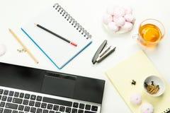 Bleistifte, ein Hefter, Knöpfe, Notizblock, Laptop, Eibische Stockfotografie