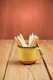 Bleistifte in einem Becher auf einem Holztisch Stockbild